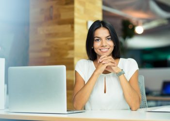 portrait of cheerful business woman sitting in office