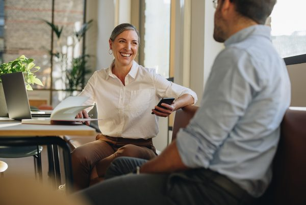 A woman sitting at a desk with a laptop on it chatting to a man sitting across from her